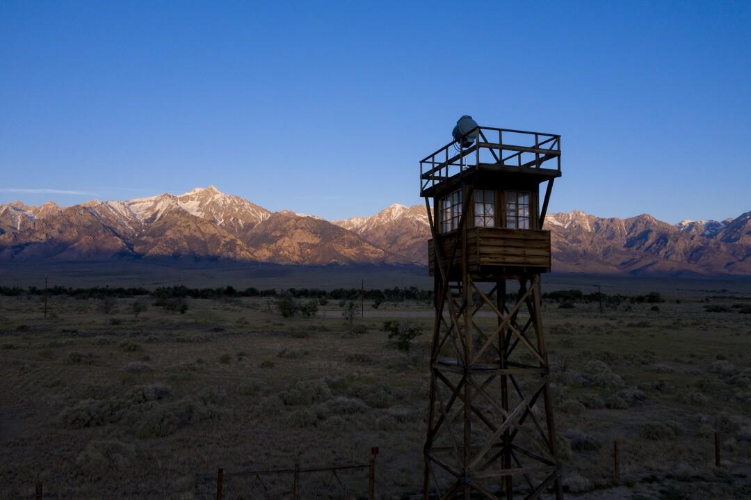 The rising sun illuminates the Sierra Nevada crest behind a restored guard tower at the Manzanar National Historic Site.