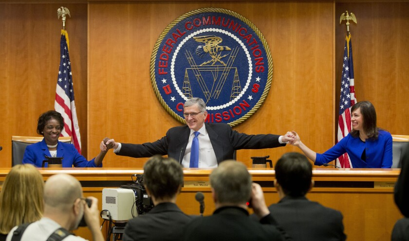 Federal Communications Commission Chairman Tom Wheeler, center, joins hands with commissioners Mignon Clyburn, left, and Jessica Rosenworcel, before a Feb. 26 meeting at which the agency approved net neutrality regulations.