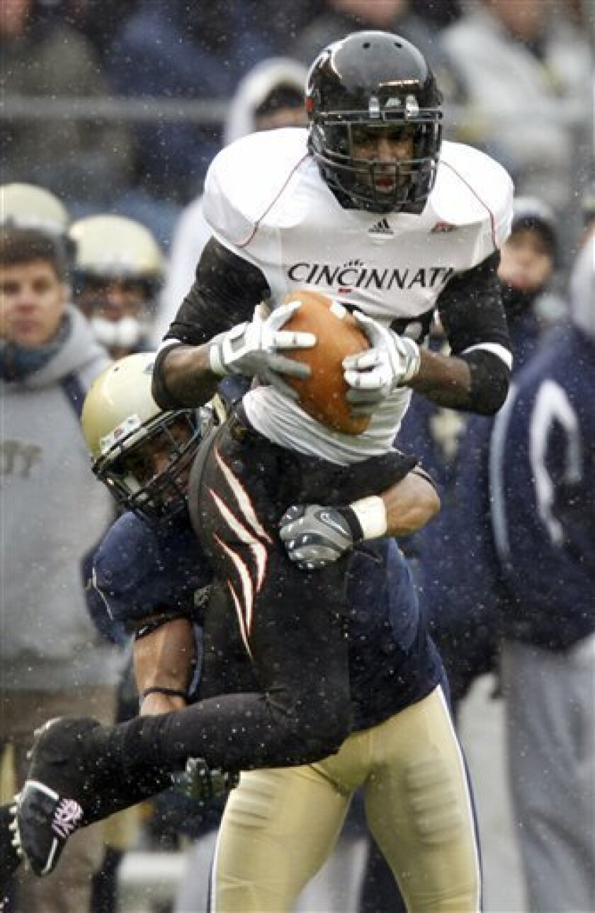 Cincinnati wide receiver Armon Binns, top, makes a catch as Pittsburgh defensive back Jovani Chapel defends during the first half of an NCAA college football game in Pittsburgh, Saturday, Dec. 5, 2009. (AP Photo/Keith Srakocic)
