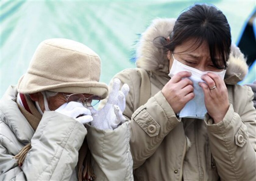 Family members cry as they pay their final respects during a burial ceremony for the March 11 tsunami victims in Higashimatsushima City, Miyagi Prefecture, Japan, Tuesday, March 22, 2011. (AP Photo/Mark Baker)