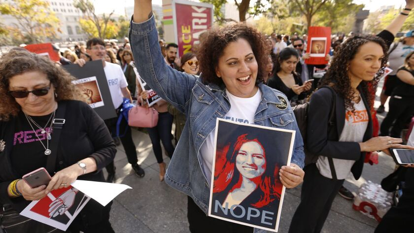 """Deputy Public Defender Alisa Blair holds a """"NOPE"""" sign with a photo of her new boss Nicole Davis Tinkham at a rally in Grand Park on Feb 12."""