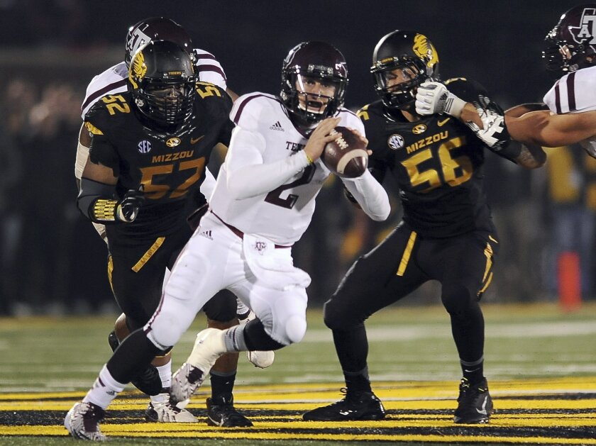 Texas A&M quarterback Johnny Manziel, center, scrambles as Missouri defensive linemen Michael Sam, left, and Shane Ray defend during the second quarter of an NCAA college football game on Saturday, Nov. 30, 2013, in Columbia, Mo. (AP Photo/L.G. Patterson)