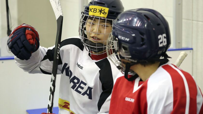A photo from the Korean Sport and Olympic Committee shows South Korean (white jersey) and North Korean (red jersey) women ice hockey team players talking during a training session in Jincheon, South Korea, on Jan. 28.