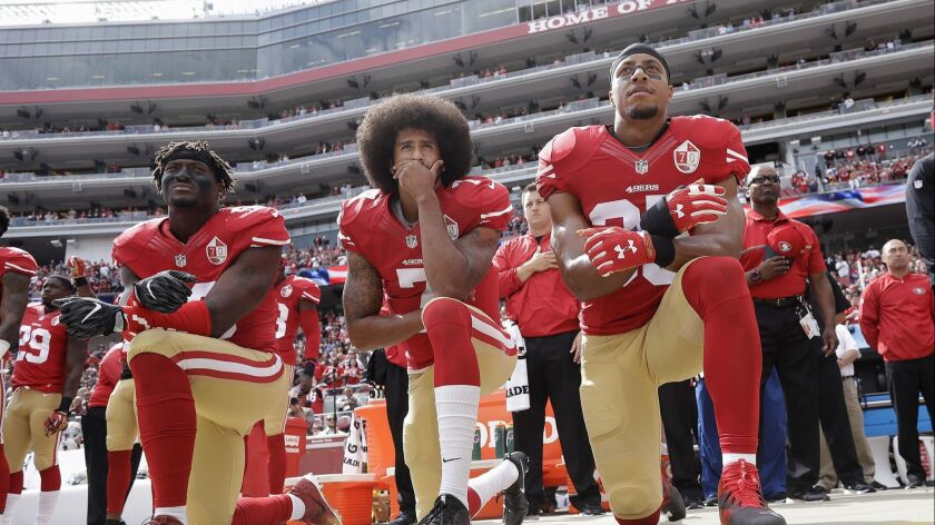 Colin Kaepernick, then-quarterback for the San Francisco 49ers, is flanked by outside linebacker Eli Harold, left, and safety Eric Reid during the national anthem before a 2016 NFL game against the Dallas Cowboys in Santa Clara.