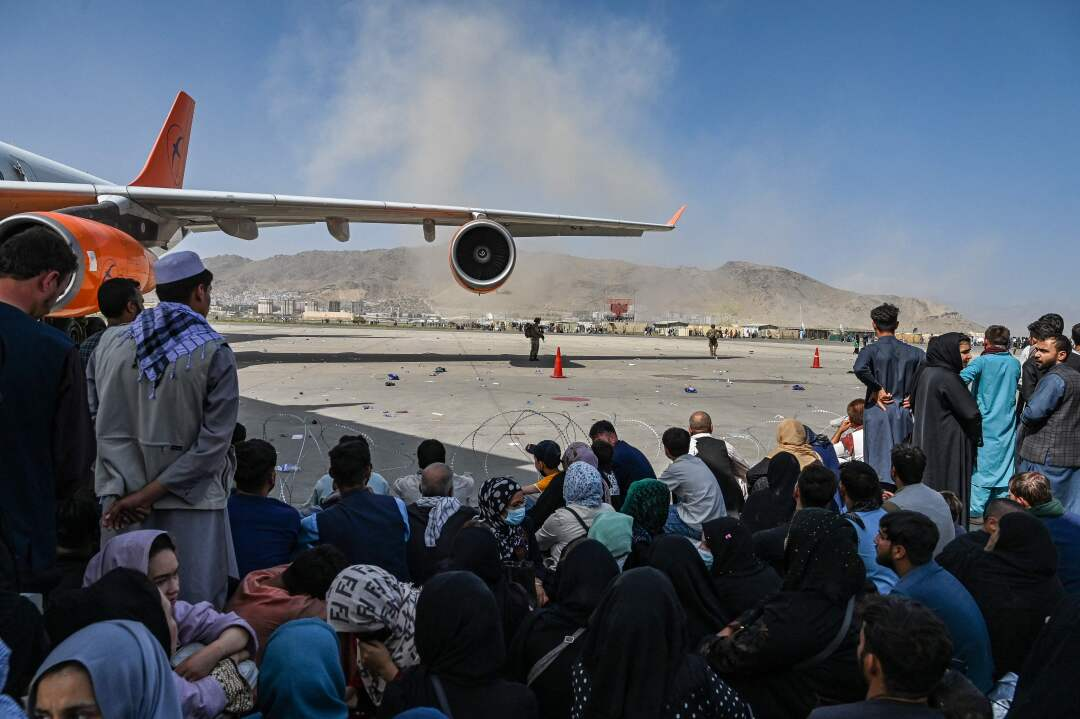 People sit at the Kabul airport.