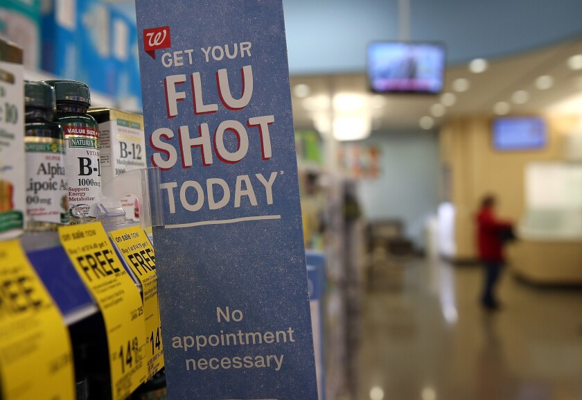 A sign advertising flu shots is displayed at a Walgreens pharmacy earlier this year in Concord, Calif.