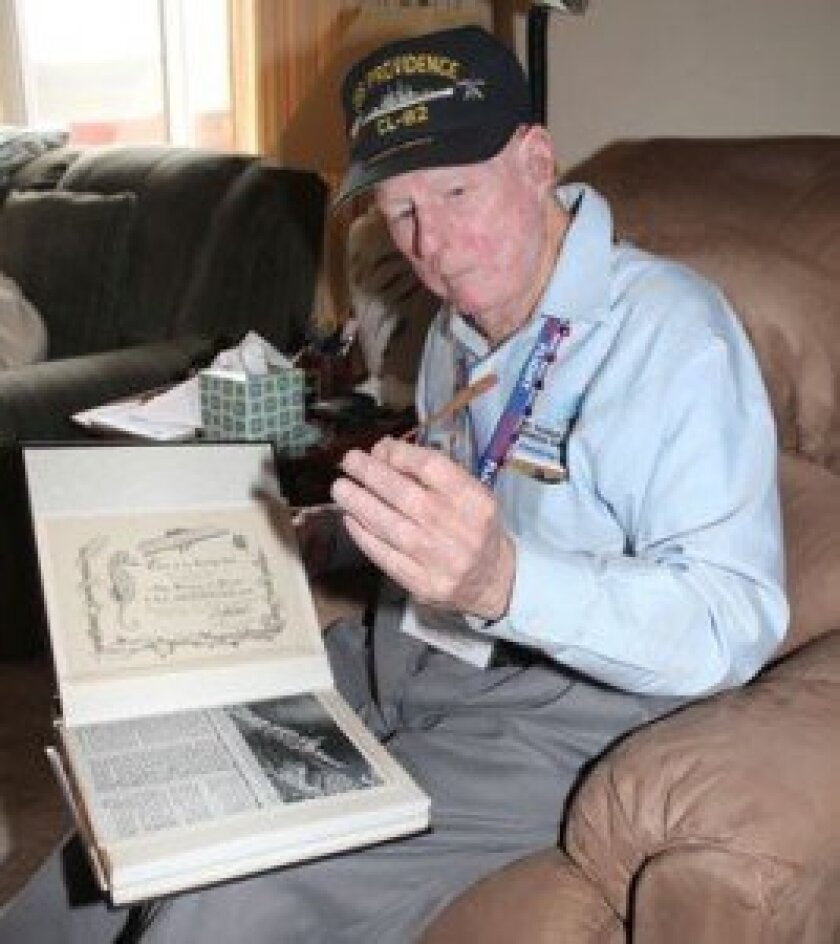 Dustin holds a piece of wood from the USS Providence. As part of its inaugural crew, Dustin served as the ship's DJ at the conclusion of World War II, while en route to the Mediterranean.