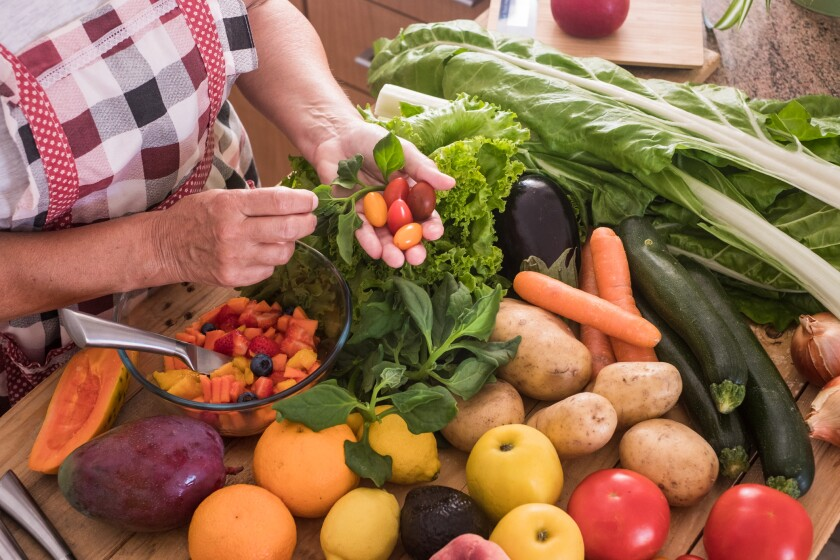 A woman choose salad ingredients from a table filled with fruits and vegetables.