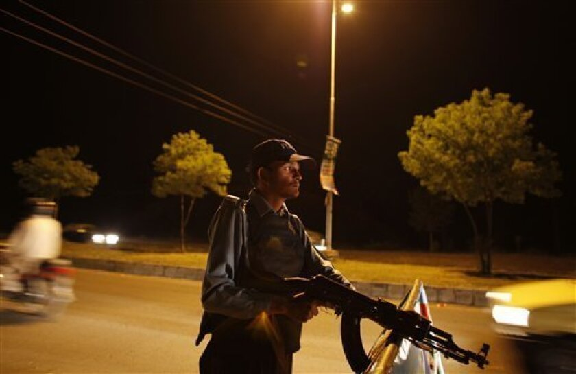 "A police officer stands guard at a check point in Islamabad, Pakistan, Tuesday, Oct. 6, 2009. Pakistan braced Tuesday for more militant attacks ahead of an anticipated offensive against a Taliban stronghold, as the insurgents said they bombed a U.N. relief agency because international aid work was not in ""the interest of Muslims."" (AP Photo/Alexandre Meneghini)"
