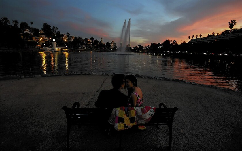 Robson Morgan and Tani Ikeda take in the sunset at Echo Park Lake. Gentrification has changed the neighborhood. Many local gang members have been forced to move to outlying areas. But their presence is still felt, officials say.