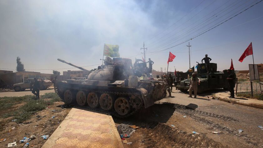 Pro-Iraqi paramilitary forces gather in a street in the town of Hatra, southwest of Mosul, on April 28, 2017.