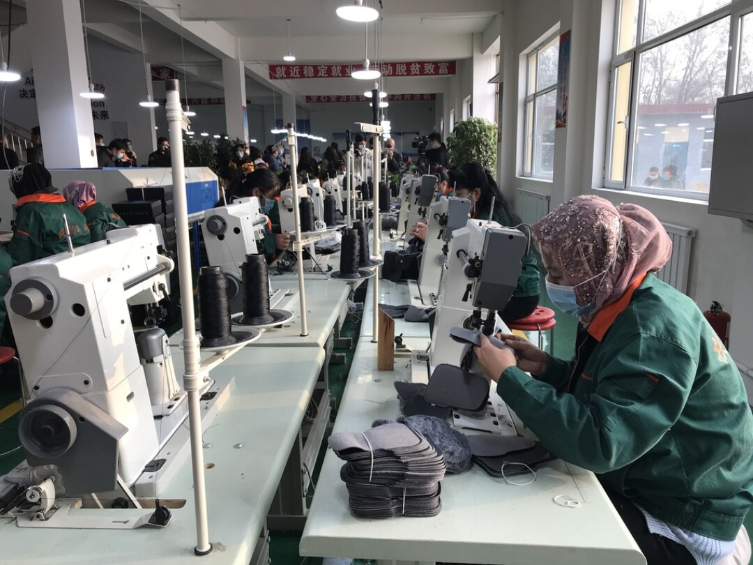 "Hui minority women sew shoe interiors together at a ""poverty alleviation factory"" on the outskirts of Linxia."