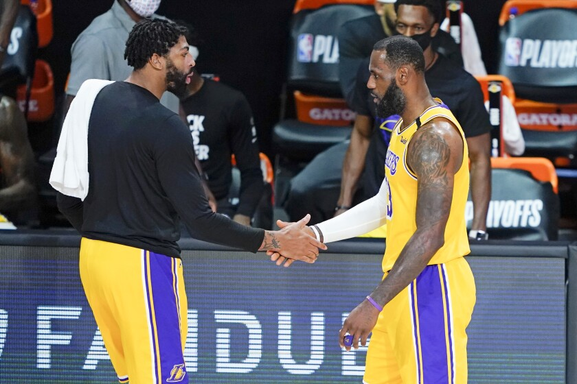 The Lakers' Anthony Davis, left, greets LeBron James as he goes to the bench during the first half Aug. 29, 2020.