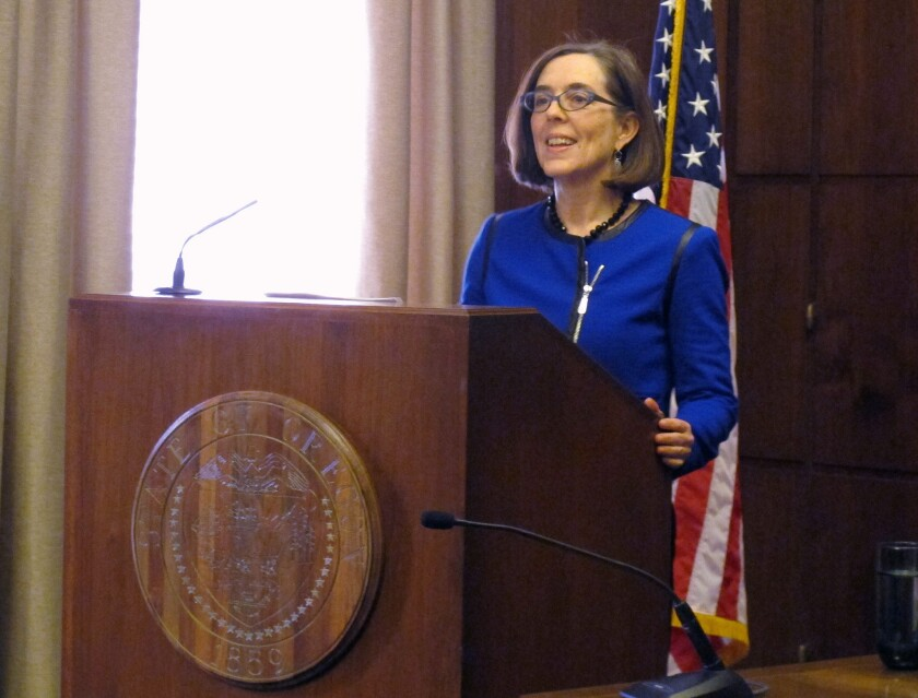 Oregon Gov. Kate Brown, shown speaking to reporters last month in Salem, on Friday signed legislation abolishing the state's troubled health insurance exchange.