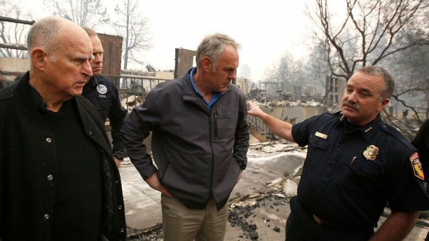 Gov. Jerry Brown and U.S. Interior Secretary Ryan Zinke tour a scorched area of Paradise, Calif., on Nov. 14, 2018.