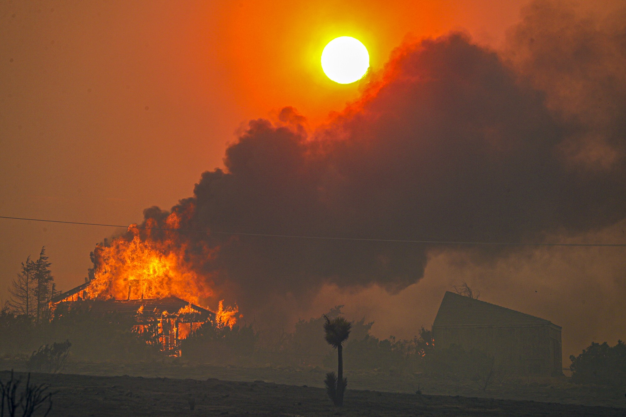 The setting sun is obscured by heavy smoke from the Bobcat fire as seen from Littlerock, Calif., on Friday.