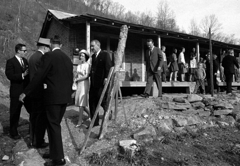 FILE - In this April 24, 1964, file photo, President Lyndon B. Johnson and his wife leave the home of Tom Fletcher, father of eight, who told Johnson he had been out of work for nearly two years, in Inez, Ky. The President made the trip to eastern Kentucky to see conditions in the Appalachian region for himself. A new study finds that the Appalachian Regional Commission's $3.8 billion investment over 50 years has helped its counties grow faster than rural areas elsewhere. But the region still lags the rest of the country in some important areas. Researchers analyzed data back to the commission's creation by Johnson in 1965. The 420-county territory includes pieces of 12 states stretching from New York to Mississippi. (AP Photo/File)