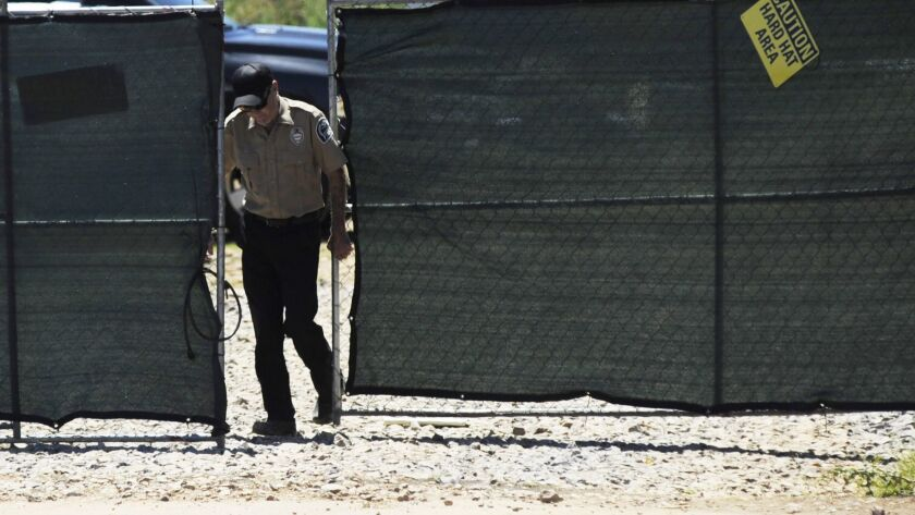 A security guard closes a gate at the construction site of a new clinic that is being built by Plann