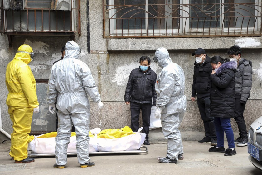 Workers stand around a body wrapped plastic