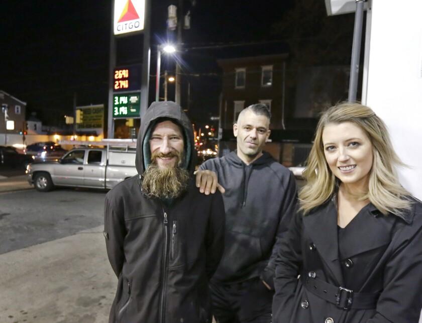Johnny Bobbitt Jr., left, Kate McClure, right, and McClure's boyfriend Mark D'Amico pose at a Citgo station in Philadelphia. Nov. 17, 2017.