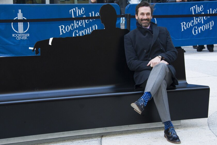"""Jon Hamm appears at an unveiling of a bench dedicated to the """"Mad Men"""" series in front of the Time & Life Building on Monday, March 23, 2015 in New York. The bench shows a silhouette of Hamm's character Don Draper. (Photo by Charles Sykes/Invision/AP)"""