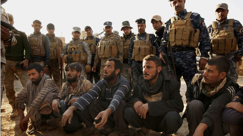 Iraqi soldiers and police detain suspects in the village of Salhiya, Iraq. The men were coming from the direction of Mosul.