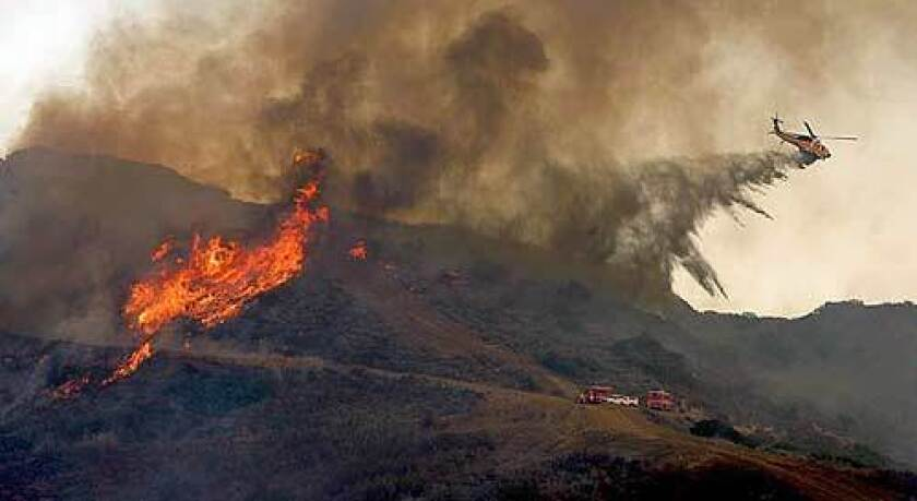 A helicopter drops water on a ridge above Latigo Canyon in Malibu, where a fast-moving brush fire threatened homes in November.