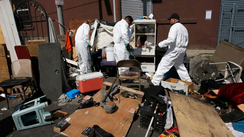 Sanitation workers clean and dispose of chemicals, human feces and sharp objects at a homeless encampment in Los Angeles last month.