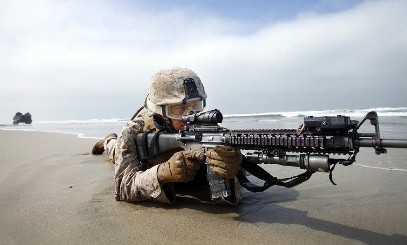 Marine Pfc. Marc Calo patrols Camp Pendleton's Red Beach in 2010 during the amphibious assault exercise Dawn Blitz. More than 5,000 sailors and Marines participated.