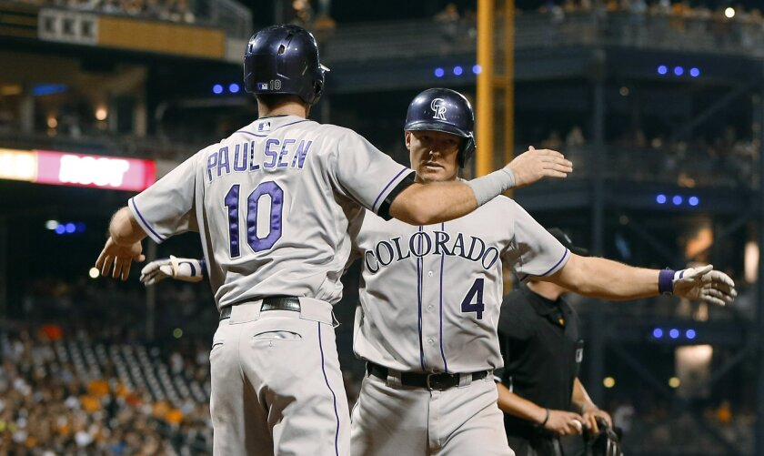 Colorado Rockies' Nick Hundley (4) is greeted by Ben Paulsen (10) after driving him in with a two-run home run during the ninth inning of a baseball game against the Pittsburgh Pirates, Saturday, Aug. 29, 2015, in Pittsburgh. The Pirates won 4-3. (AP Photo/Keith Srakocic)