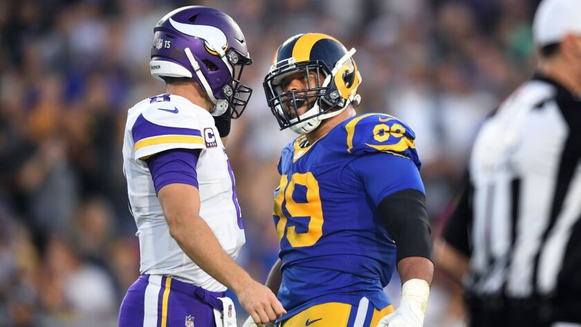 Rams defensive tackle Aaron Donald has a few words with Vikings quarterback Kirk Cousins at the Coliseum.