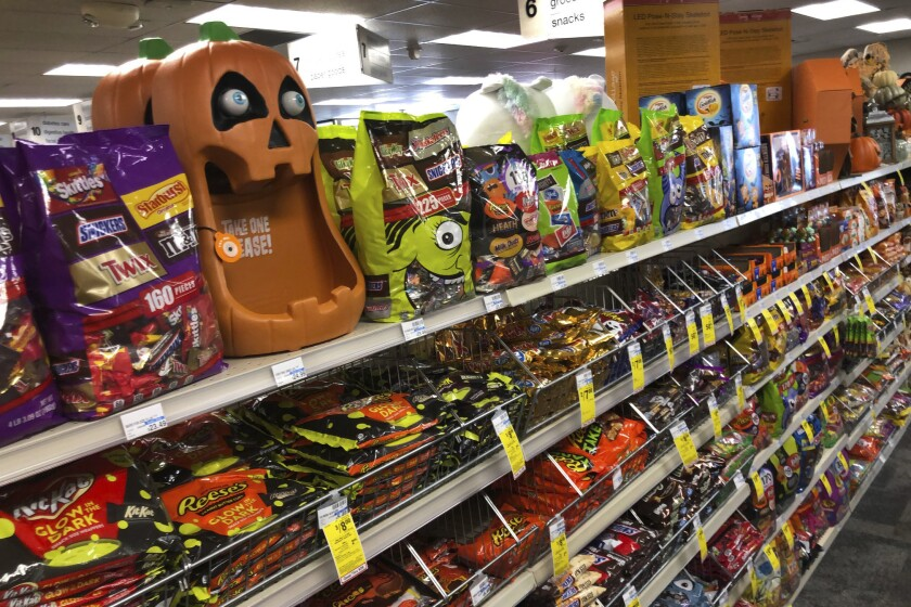 Halloween candy and decorations are displayed at a store, Wednesday, Sept. 23, 2020, in Freeport, Maine. U.S. sales of In this year of the pandemic, with trick-or-treating still an uncertainty, Halloween candy were up 13% over last year in the month ending Sept. 6, according to data from market research firm IRI and the National Confectioners Association. (AP Photo/Robert F. Bukaty)