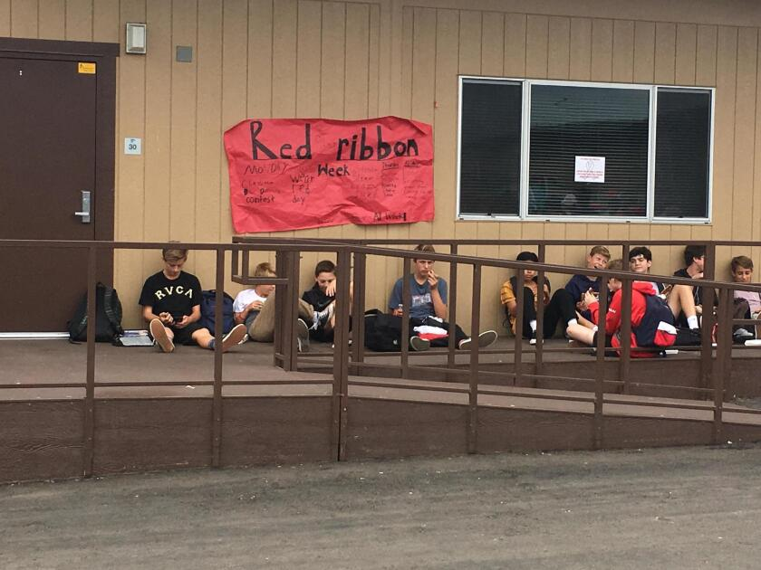 Earl Warren students watch the show near a banner for Red Ribbon Week.