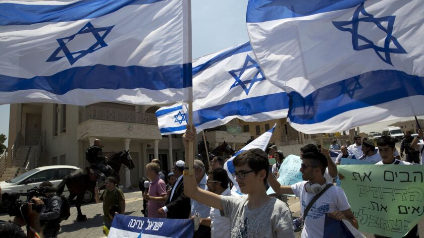 Activists carry Israeli flags in the Israeli Arab town of Umm El Fahem on Aug. 9.