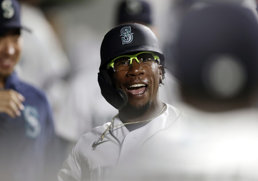 Seattle Mariners' Shed Long Jr. celebrates in the dugout after hitting a solo home run on a pitch from Colorado Rockies' Tyler Kinley during the eighth inning of a baseball game, Tuesday, June 22, 2021, in Seattle. (AP Photo/John Froschauer)