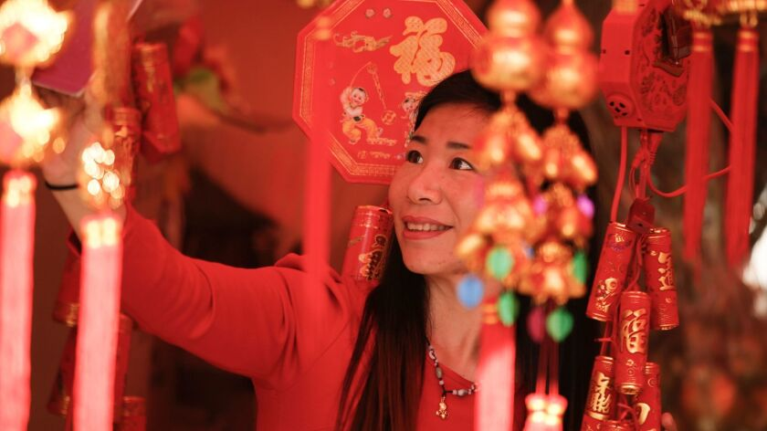 Lily Ting Ma of China takes a selfie in one of the souvenir booths selling Lunar New Year items in the Flower Festival.