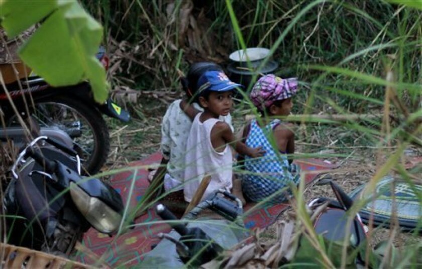 In this April 30, 2013 photo, Muslim children take refuge in forests along a road in Okkan, about 70 miles (110 kilometers) north of Yangon, Myanmar. Buddhist mobs hurling bricks overran a pair of mosques and set hundreds of homes ablaze in central Myanmar on Tuesday, injuring at least 10 people in