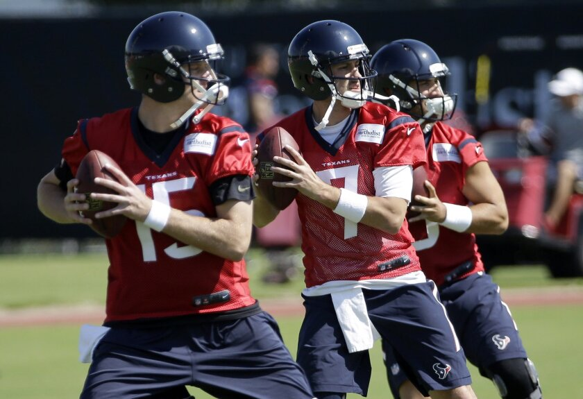 FILE - In this June 1, 2015, file photo, Houston Texans quarterbacks, from left to right, Ryan Mallett, Brian Hoyer and Tom Savage drop back during an NFL football organized team activity in Houston. Hoyer was terrible in his Houston debut and was benched for Mallett in the fourth quarter in a loss to Kansas City on Sunday, Sept. 13, 2015. Now coach Bill O'Brien must decide to stick with Hoyer this week or give Mallett a chance. (AP Photo/David J. Phillip, File)