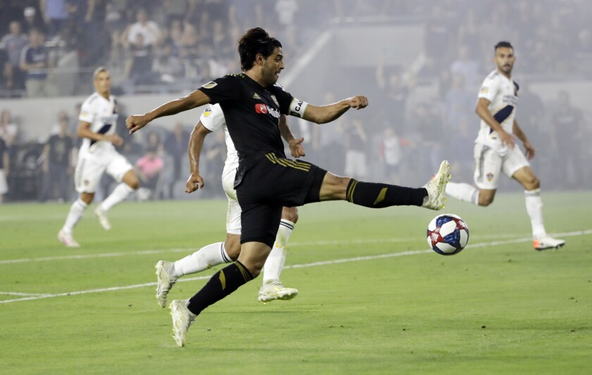 LAFC's Carlos Vela takes a during the second half of Sunday's 3-3 tie against the Galaxy. Vela exited the game in the 61st minute after suffering a hamstring injury.