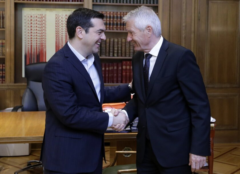 Greece's Prime Minister Alexis Tsipras, left, and Council of Europe Secretary General Thorbjorn Jagland shake hands during their meeting at the Maximos Mansion in Athens, Wednesday, May 25, 2016. Jagland told The Associated Press in an interview on Wednesday, that Greece has faced major problems in dealing with the refugee crisis but that the country has made significant efforts to handle the issues, although concerns remain about the detention of some asylum-seekers while their applications are being processed. (AP Photo/Thanassis Stavrakis)
