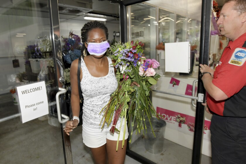 People wait in line at a mask distribution event in Miami on June 26. Coronavirus cases are climbing in Florida.