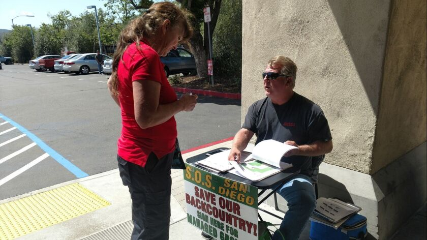 Paid signature gatherer Tom Elsey solicits John Hancocks for the Safeguard Our San Diego Countryside initiative outside a Poway supermarket last month.