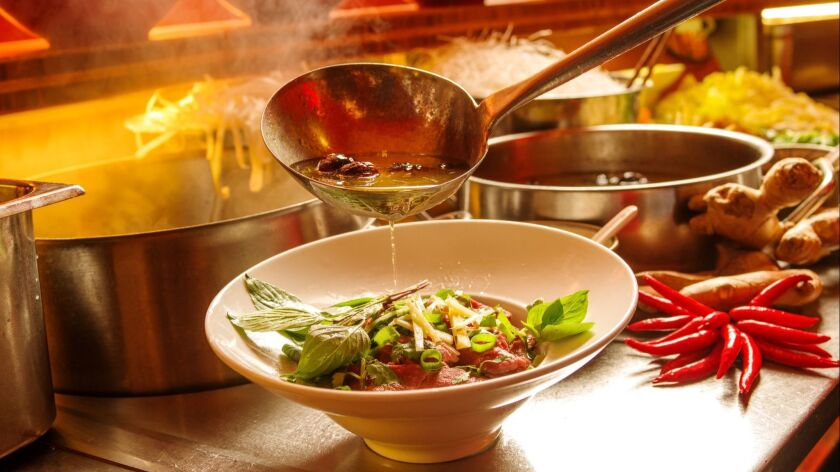 Preparation of Pho Bo. Hot broth is added to cook the thin strips of beef to perfection. Credit: Man
