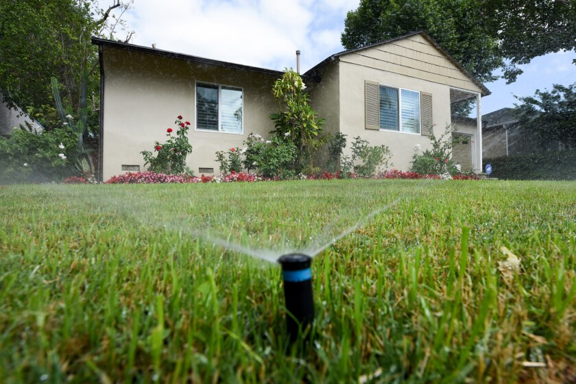 Sprinklers water the front lawn of a house on Zelzah Avenue in Encino earlier this year.
