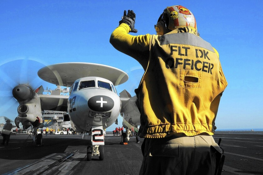 A U.S. sailor directs an aircraft aboard the carrier George H.W. Bush in the Persian Gulf, where it is positioned to support Iraqi government forces if needed.
