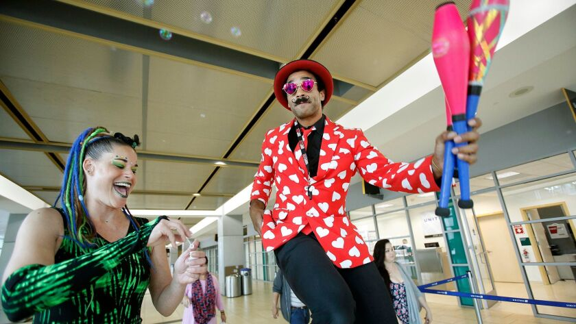 """Performers J7 , left, blows bubbles as Alexander""""The Amazing"""" Knapp rides high on a unicycle in terminal 2 at Lindbergh Field."""