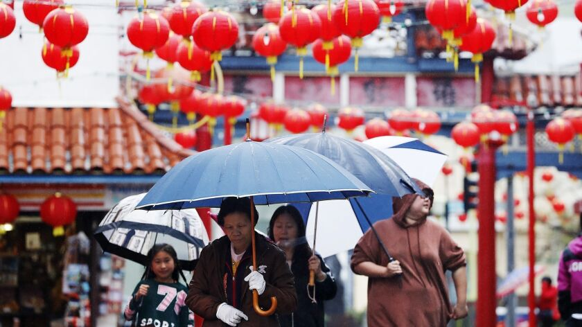 Visitors to downtown Los Angeles' Chinatown walk in the rain Saturday. Another atmospheric river-fueled storm is expected to hit Southern California on Tuesday.