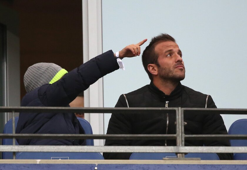 Hamburg's former player Rafael van der Vaart and his son Damian  sit in the stands during the German Bundesliga  soccer  match between Hamburger  SV and Borussia Moenchengladbach  in Hamburg, Germany,  Sunday Feb. 14, 2016. (Christian Charisius/dpa via AP)