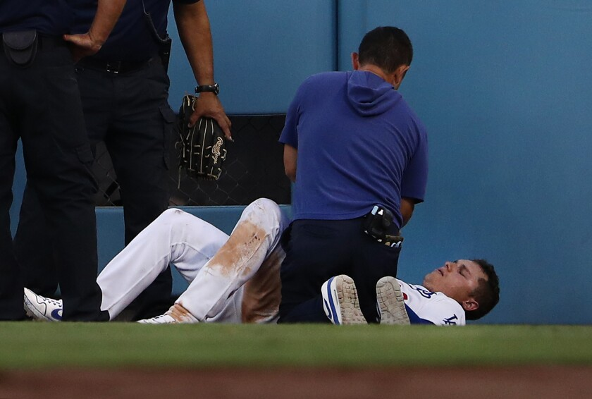 Joc Pederson is tended to after crashing into the fence.