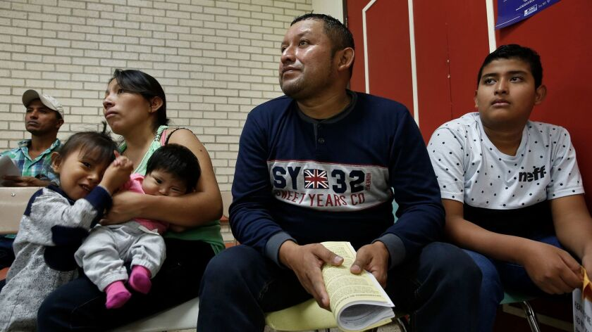 Miguel Rodas. center, and his son, Samuel, right, of El Salvador, listen to information about their court hearings, that will occurring in coming months. At left are Faviola, the mother of 2-month-old Kimberly, and Genesis, 3.